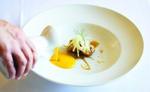 Fall carrot soup with curry, orange, and cider poured over pork belly croquette and apple salad at the tableside.